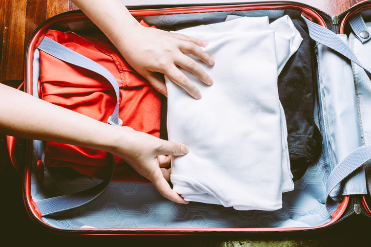 Woman's hands packing a luggage